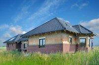Budowa ściany trójwarstwowej w dwóch etapach izolację z wełny i elewację układa się dopiero po pokryciu dachu